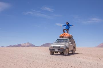 Homme veste bleu sur voiture 4x4 dans le désert en Bolivie