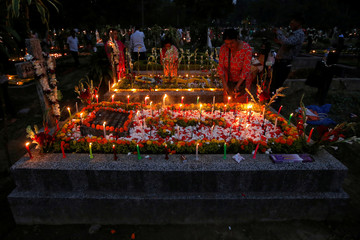 People burn incense sticks and light candles on the graves of their relatives at a cemetery during the observance of All Souls Day, in Kolkata