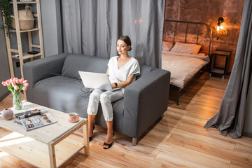 Young woman in white clothes sitting on the couch with laptop at the living room of the modern loft apatment