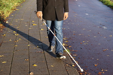A blind person walking on the street using a red and white walking stick.
