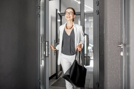 Young business woman in white suit going out of the residential building hurrying to work