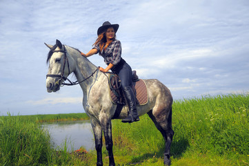 girl in plaid shirt and cowboy hat riding a horse by the lake