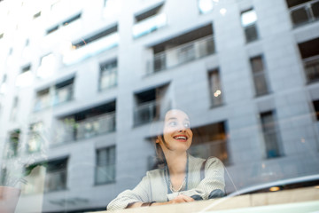 View through the window on the stylish woman sitting indoors with modern building on the reflection. Wide view with copy space