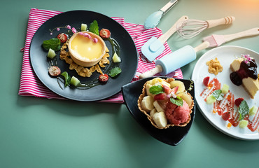 The fruit ice cream in waffle basket put at the middle of lemontart dish and cheese cake dish,on table