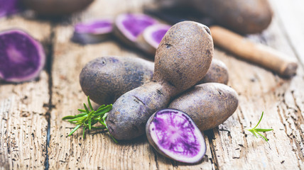 Vitolette noir or purple potato. On a wooden background.