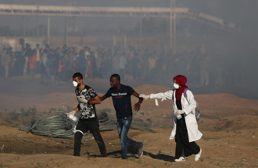 Palestinian reacts from tear gas fired by Israeli troops during a protest at the Israel-Gaza border fence in Gaza