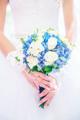 Hands of the bride with a delicate wedding bouquet. Soft selective focus.