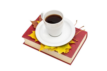 Cup of coffee with autumn leaves on book. Isolated on white.