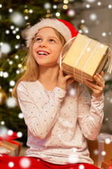 christmas, holidays and childhood concept - smiling girl in santa helper hat with gift box at home