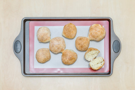 freshly baked buns on a silicone baking mat, on an iron tray
