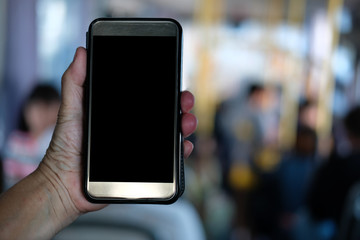 hand holding smartphone while riding on commuter bus. people traveling by public transport with mobile phone