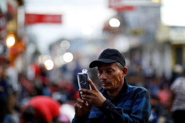 A man part of a caravan travelling to the U.S., takes a pictures as he waits to get into Mexico, near the border gate between Guatemala and Mexico, in Tecun Uman