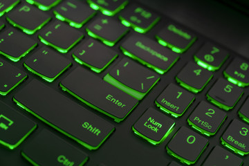 Colorful keyboard for gaming. Backlit keyboard with green color scheme. Colorful light keyboard