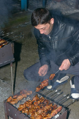 Mature man is cooking barbecued meat on mangal with skewers.
