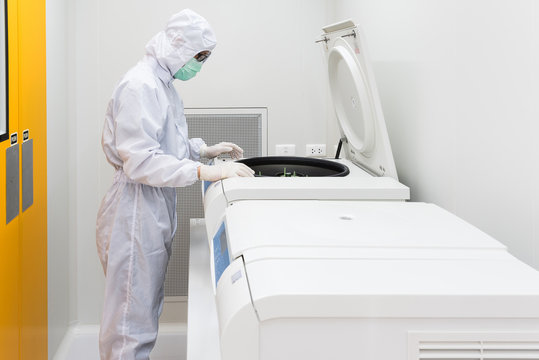 A scientist in sterile coverall gown using laboratory equipment for doing biological research in cleanroom.