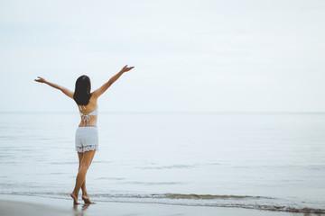 Travel woman walking on beach in sunset