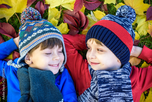 95d95963cb1 Happy siblings having fun in autumn park on warm day. Healthy children  scarf and hat with maple foliage