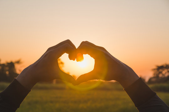 Hands making heart shape with sunset. Close up of woman hands making heart shape gesture.