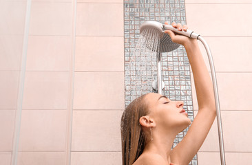 Beautiful young woman taking shower at home