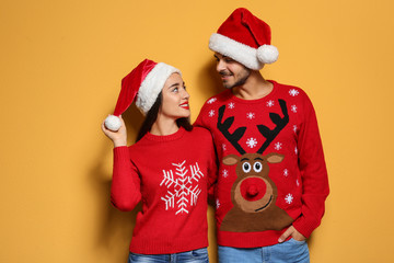 Young couple in Christmas sweaters and hats on color background