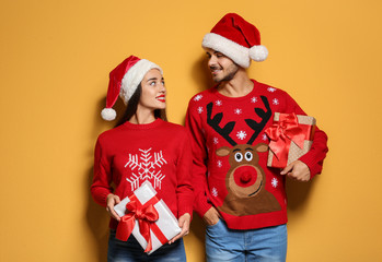 Young couple in Christmas sweaters and hats with gifts on color background