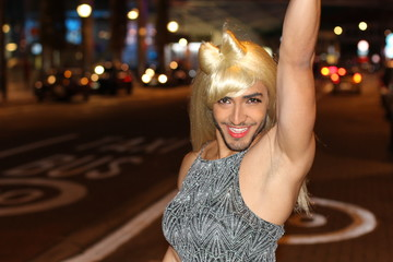 Ecstatic muscular transvestite with beard and blonde wig