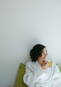 Relaxed woman drinking tea in robe at the spa