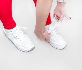 Girl tying white sneakers on a light background