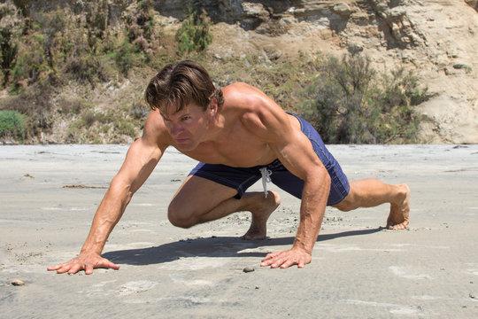 Muscular Caucasian man doing tough bear crawl workout