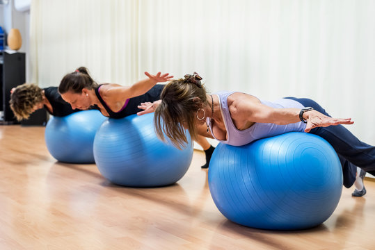 Group of fit ladies in gym using fit balls