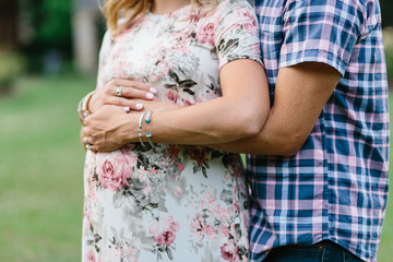 Man and woman holding hands over pregnant belly