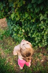 Toddler girl looking up at a big lilac bush.