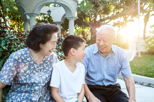 Happy Senior Asian Couple Talking With Their Grandchild