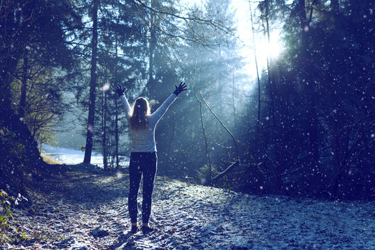 Woman raises her hands and breathing cold air during a sunny winter morning during snowfall. Selective focus used