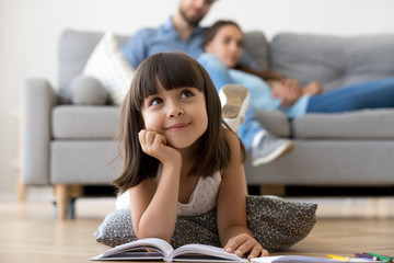 Close up little adorable thoughtful smiling daughter dreaming lying at cushion on warm floor with book in living room at modern home, resting married couple parents on background, focus on small kid