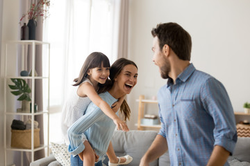 Young happy mother laughing carrying on back piggybacking little daughter catching dad playing with diverse family having fun together. Kid enjoying active games with parents in living room at home