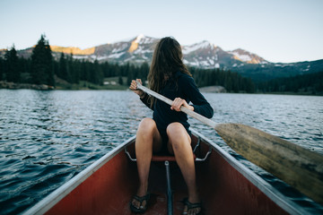 Woman rowing boat with mountains in background