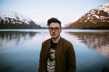 Young man with snow capped mountains and a lake in the background