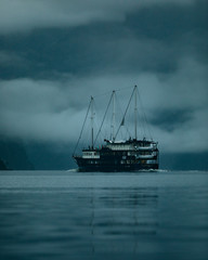 Boat sailing on water with dark skies