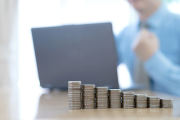 Businessman with working at workplace. coins stack