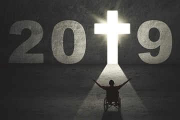 Disabled man with cross symbol and number 2019