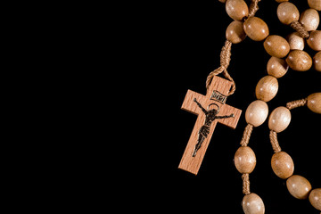 A brown rosary lying on a black background