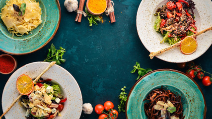 A set of dishes. Pasta with parmesan cheese and vegetable salad and blue cheese. Top view. Free space for your text. On a wooden background.