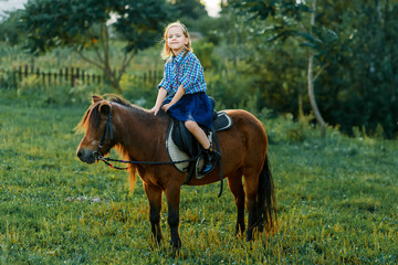 A girl and a pony outside at sunset. Nature near the water