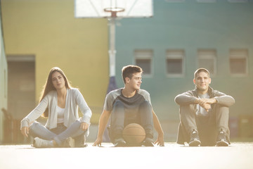 Three friends sitting on the basketball court