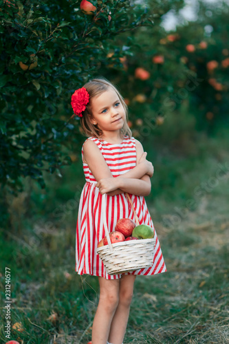 3d8066e76b2 A girl in a red dress and with red flower in her hair in the apple ...