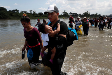 Central American migrants cross the Suchiate River, the natural border between Guatemala and Mexico