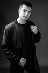 Studio shot of young handsome man in black and white