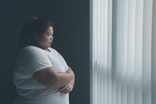 Lonely obese woman standing near the window
