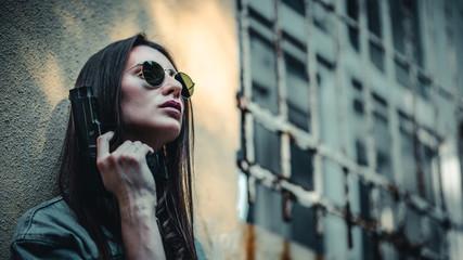 beautiful girl with a gun in her hand posing near the wall